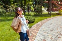 Junge gl?ckliche Frau, die Einkaufspapiert?ten im Sommerpark h?lt und modische Ausstattung tr?gt lizenzfreies stockbild