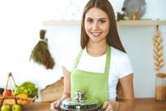 Junge gl?ckliche Frau, die Suppe in der K?che kocht Gesunde Mahlzeit, Lebensstil und kulinarisches Konzept L?chelndes Kursteilneh stockfoto