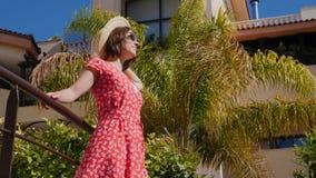 Junge gl?ckliche Frau genie?t die Sonnenstellung im Hotelgarten mit den Palmen, die rotes Kleid, Hut und Sonnenbrille tragen Lang stock video
