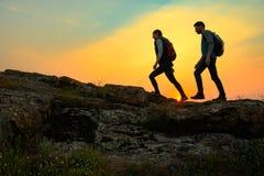 Junge gl?ckliche Reisende, die mit Rucks?cken auf Rocky Trail bei Sommer-Sonnenuntergang wandern Familien-Reise-und Abenteuer-Kon lizenzfreie stockfotos