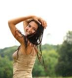 Junge glückliche Frau, die in den Regen geht Stockfotos