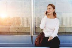 Junge glückliche Frau, die am Handy mit ihrem Freund während sie ein Taxi oder auf einen Bus auf einer Station wartend spricht Stockfoto