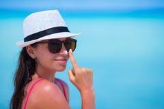Junge glückliche Frau, die Sonnenschutzmittel auf ihr anwendet Stockbilder