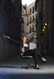Junge glückliche Geschäftsfrau, die auf Büro-Stuhl auf Straße mit Laptop sitzt Stockfotos