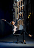 Junge glückliche Geschäftsfrau, die auf Büro-Stuhl auf Straße mit Laptop sitzt Lizenzfreie Stockfotografie