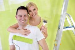 Junge glückliche handliche Paare, die neues Haus malen Stockfoto
