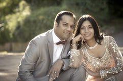 Junge glückliche indische Paare, die zusammen draußen sitzen Lizenzfreies Stockfoto