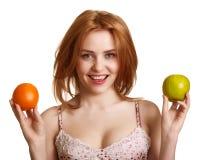 Junge glückliche lächelnde Frau mit Apfel und Orange Lizenzfreies Stockbild