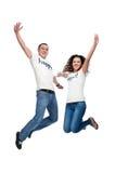 Junge glückliche Paare, die oben springen Stockfoto