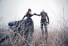 Junge goth Paare, die auf Feld gehen Stockbild