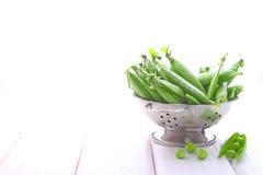 Junge grüne Erbsen in einem Metallsieb lizenzfreie stockfotos