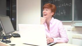 Junge Grasendateien des weiblichen Lehrers beim Sitzen am Schreibtisch mit Laptop im modernen Klassenzimmer stock video