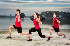 Junge Gruppe, die Barbellgewicht aufhebt Stockfoto