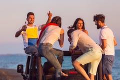 Junge Gruppe, die Spaß auf dem Strand hat und in ein konvertierbares Auto tanzt Stockbilder