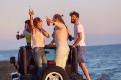 Junge Gruppe, die Spaß auf dem Strand hat und in ein konvertierbares Auto tanzt Stockfotos