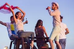 Junge Gruppe, die Spaß auf dem Strand hat und in ein konvertierbares Auto tanzt Lizenzfreie Stockfotos