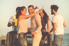 Junge Gruppe, die Spaß auf dem Strand hat und in ein konvertierbares Auto tanzt Lizenzfreie Stockbilder
