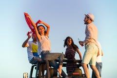 Junge Gruppe, die Spaß auf dem Strand hat und in ein konvertierbares Auto tanzt Stockbild
