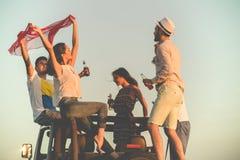 Junge Gruppe, die Spaß auf dem Strand hat und in ein konvertierbares Auto tanzt Lizenzfreie Stockfotografie