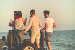 Junge Gruppe, die Spaß auf dem Strand hat und in ein konvertierbares Auto tanzt Stockfoto