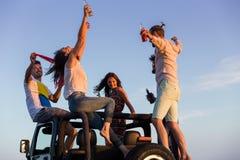 Junge Gruppe, die Spaß auf dem Strand hat und in ein konvertierbares Auto tanzt Lizenzfreies Stockfoto