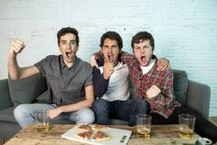 Junge Gruppe glückliche und aufgeregte Männer, die ein Fußballspiel auf der Couch aufpassen stockfotografie