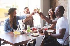 Junge Gruppe lächelnde Freunde, die Gläser klirren stockfoto