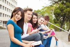 junge Gruppe Studenten, die auf der Treppe sitzen Stockfotografie