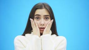 Junge gute Geschäftsmädchenstellung auf einem blauen Hintergrund Während ihrer Überraschung setzt sie ihre Hände auf ihre Backen stock footage