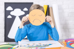 Junge hält eine Papiermaske mit traurigem Gesicht Stockfotos