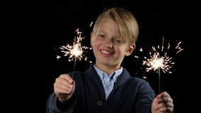 Junge hält eine Wunderkerze in beiden Händen und lächelt Schwarzer Hintergrund stock video footage