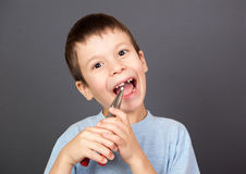 Junge hält einen verlorenen Zahn in den Zangen Lizenzfreie Stockfotos