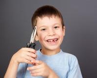 Junge hält einen verlorenen Zahn in den Zangen Stockfotografie
