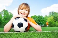 Junge hält Fußball mit dem Verbiegen in Ellbogenarme Lizenzfreie Stockfotos
