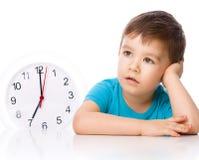 Junge hält große Uhr Stockbilder