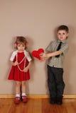 Junge hält rotes Inneres für Mädchen an Stockfotografie
