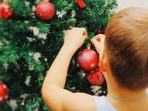 Junge hängt Ball auf dem Weihnachtsbaum Rückseitige Ansicht Lizenzfreie Stockbilder