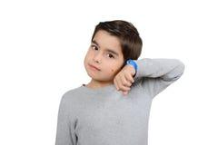Junge hört auf die Uhren, die auf Weiß lokalisiert werden Lizenzfreie Stockfotografie