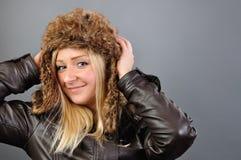 Junge, hübsche, blonde Frau in der Pelzschutzkappe untersucht die Kamera. Lizenzfreie Stockfotos