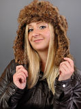 Junge, hübsche, blonde Frau in der Pelzschutzkappe untersucht die Kamera. Stockfoto