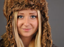 Junge, hübsche, blonde Frau in der Pelzschutzkappe untersucht die Kamera. Stockfotografie