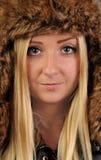 Junge, hübsche, blonde Frau in der Pelzschutzkappe untersucht die Kamera. Stockfotos