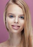 Junge hübsche Blondine mit dem Frisurabschluß hoch und Make-up auf dem rosa Hintergrundlächeln Lizenzfreie Stockfotografie