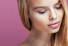 Junge hübsche Blondine mit dem Frisurabschluß hoch und Make-up auf dem rosa Hintergrundlächeln Lizenzfreies Stockbild