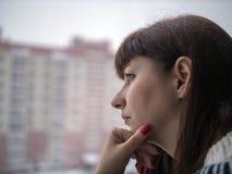 Junge hübsche brunette Frau mit langen Haarblicken durchdacht bei der Stellung an der Fensternahaufnahme lizenzfreie stockfotos