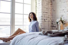 Junge hübsche Brunettefrau in ihrem Schlafzimmer, das am Fenster, glückliches lächelndes Lebensstilleutekonzept sitzt Lizenzfreie Stockbilder