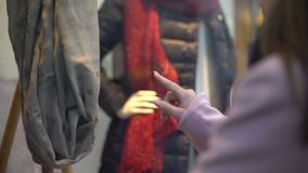 Junge hübsche Dame, die Kleidung im Geschäftsfenster, träumend, um zu kaufen, kein Geld betrachtet stock video footage