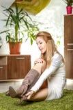 Junge hübsche Frau, die auf dem grünen Teppich in ihrem Wohnzimmer sitzt Stockfotografie