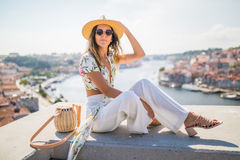 Junge hübsche Frau, die auf dem Standpunkt vor dem Duero-Fluss und Brücke Dom Luis I in Porto, Portugal sitzt Lizenzfreies Stockfoto