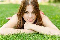 Junge hübsche Frau, die auf grünem Gras im Park liegt Stockfotos